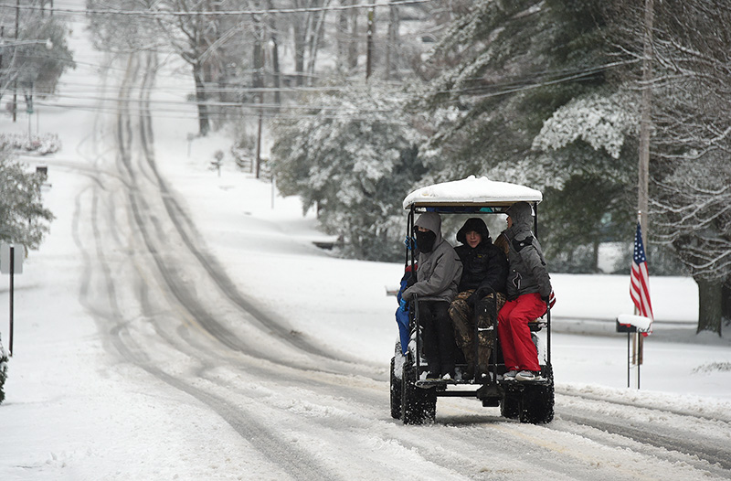Braving icy roads, boys in Gadsden, Alabama take a wintery ride on Wednesday.