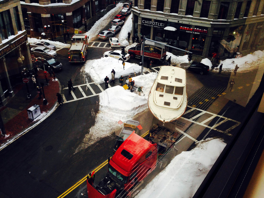 In this photo taken through a window, a large truck towing an even bigger boat broke down in downtown Boston, snarling traffic in the heart of the city's Financial District on Wednesday.