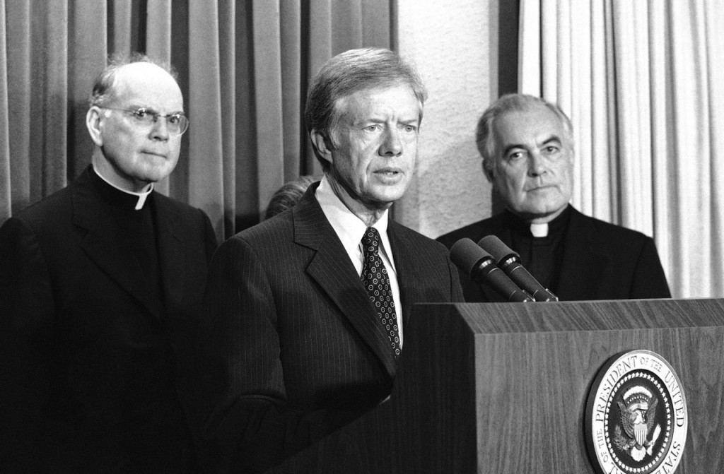 President Jimmy Carter announces a pledge of $67 million in humanitarian relief for Cambodia at the White House on Oct. 24, 1979. Standing at right is The Rev.  Theodore M. Hesburgh, president of Notre Dame University. At left is Cardinal Terence Cooke. The Associated Press