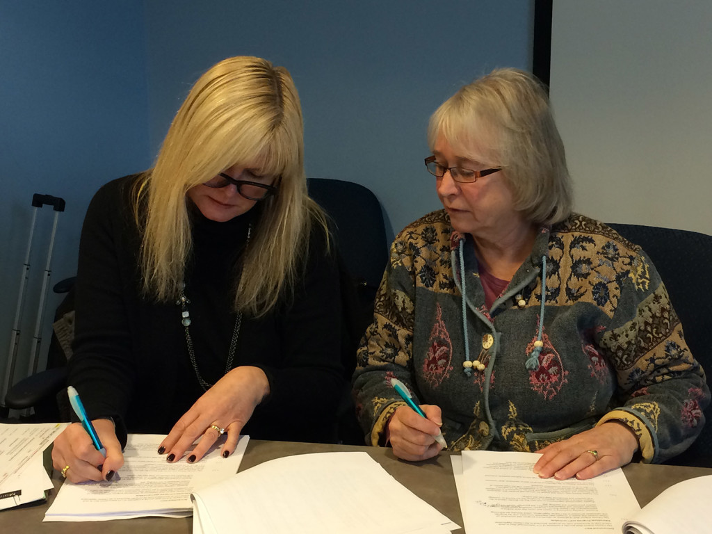 Maine Virtual Academy board Chairwoman Amy Carlisle, left, signs the contract opening the state's second virtual charter school as Maine Charter School Commission Chairwoman Shelley Reed looks on.