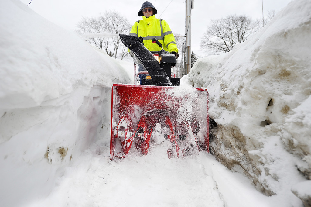 Harvey Rice, a maintenance technician for Goodwill Industries on Forest Avenue, seems to be snowblowing in a canyon as the walls of snow built up from previous storms frame his early-morning snow clearing from the sidewalks around the property Wednesday.