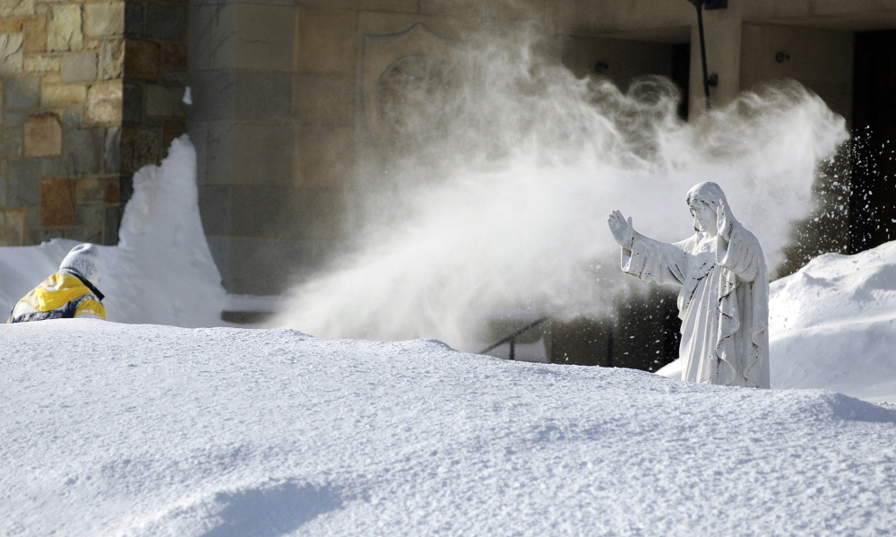 George Blomquist clears snow at Our Lady of the Angels Church after a weekend storm in Worcester, Mass. Churches, synagogues and mosques in New England report that attendance is down at services this winter, since many storms have hit on or close to days of worship. Meanwhile, costs for snow removal, heating and maintenance are soaring.