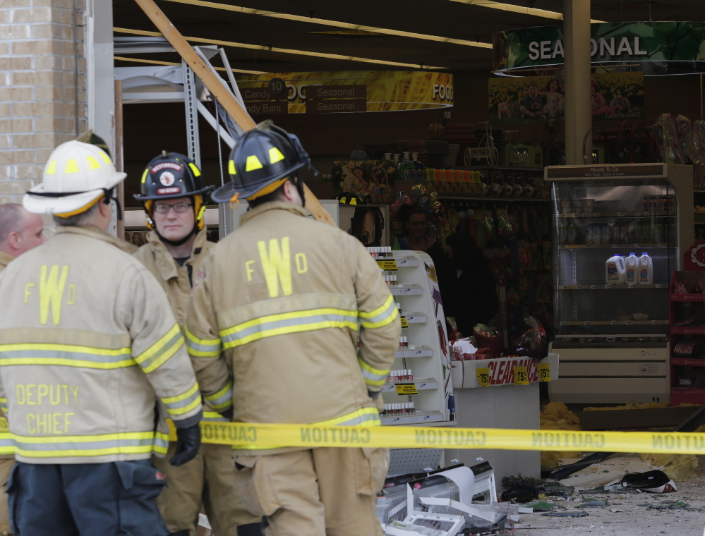 Firefighters secure the scene of an accident on Main Street in Westbrook Sunday involving a vehicle that crashed through the storefront of the Rite Aid.