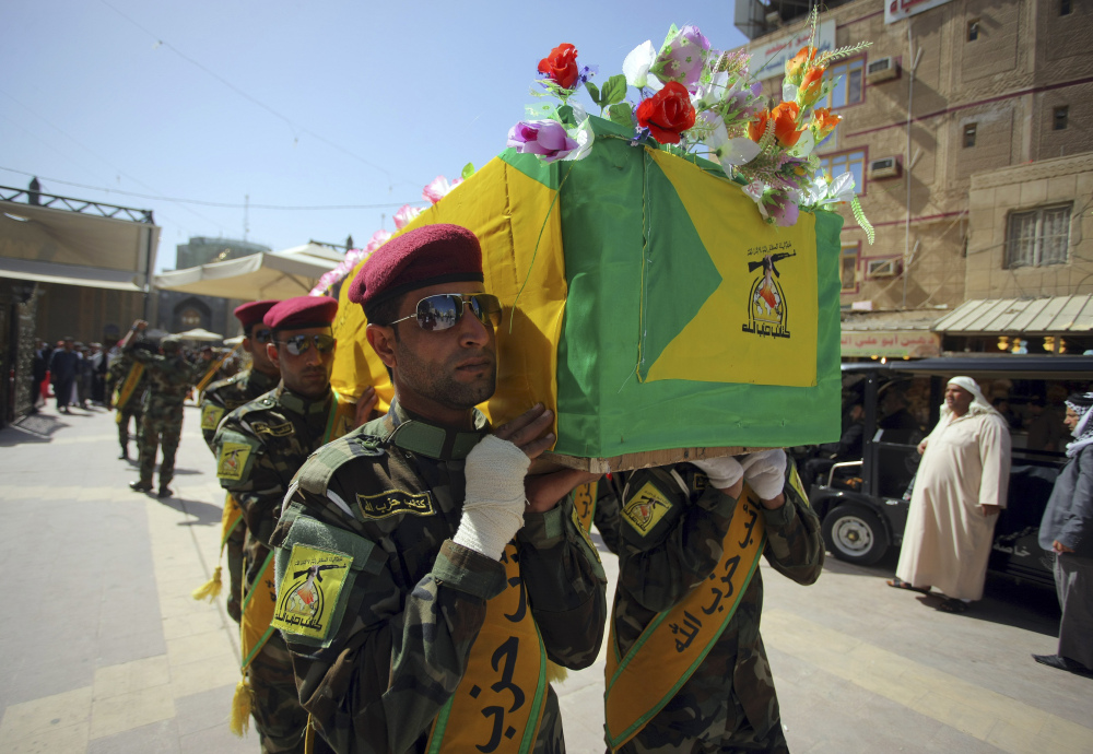 Iraqi Hezbollah fighters carry the coffin of their comrade Ali Mansour, who his family says was killed in Tikrit fighting Islamic militants, during his funeral procession Monday in Najaf.