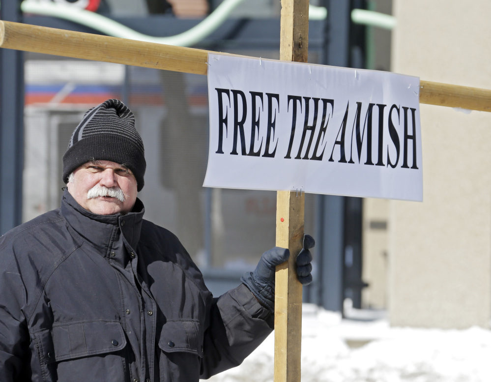Werner Lange holds a sign outside federal court in Cleveland on Monday. Sixteen Amish men and women were resentenced after a federal appeals court last year dismissed all of their hate crimes convictions in the 2011 attacks in which they chopped off the beards and hair of others with whom they disagreed.