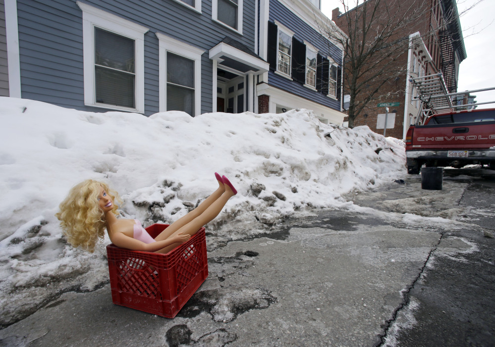 A fashion doll in a milk crate saves a parking space on a residential street in South Boston, preserving the unwritten rule: If you shoveled it out, it's yours.
