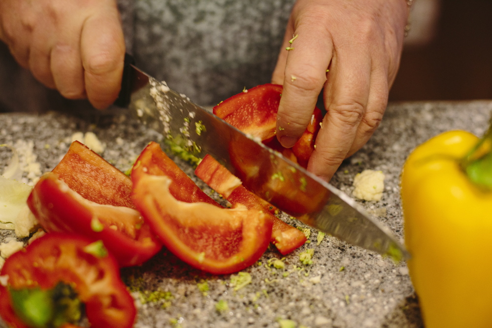 Julie Johnson slices red pepper for a roast vegetable dish. Whitney Hayward/Staff Photographer