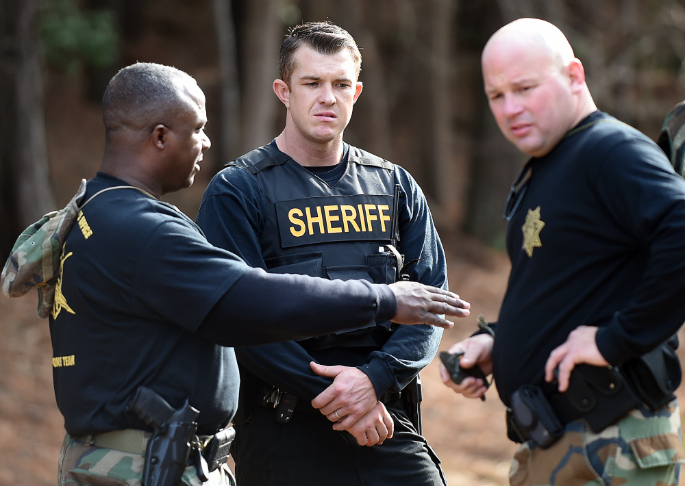 Wilson County sheriff's deputies investigate an area near Interstate 95  in Wilson, N.C., on Monday. Armed robbers hijacked an armored truck, tied up the two guards and disappeared with 275 pounds of gold bars. Associated Press/The Wilson Times, Brad Coville