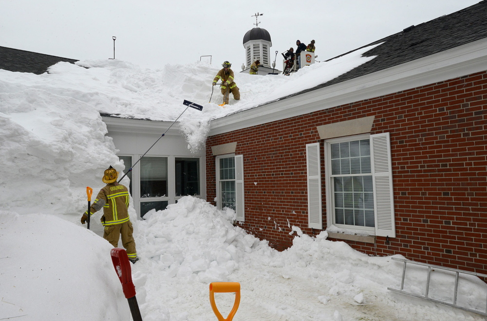 Firefighters from Ogunquit and Wells shovel snow off the Wells Public Library on Thursday after the roof bowed under the weight.