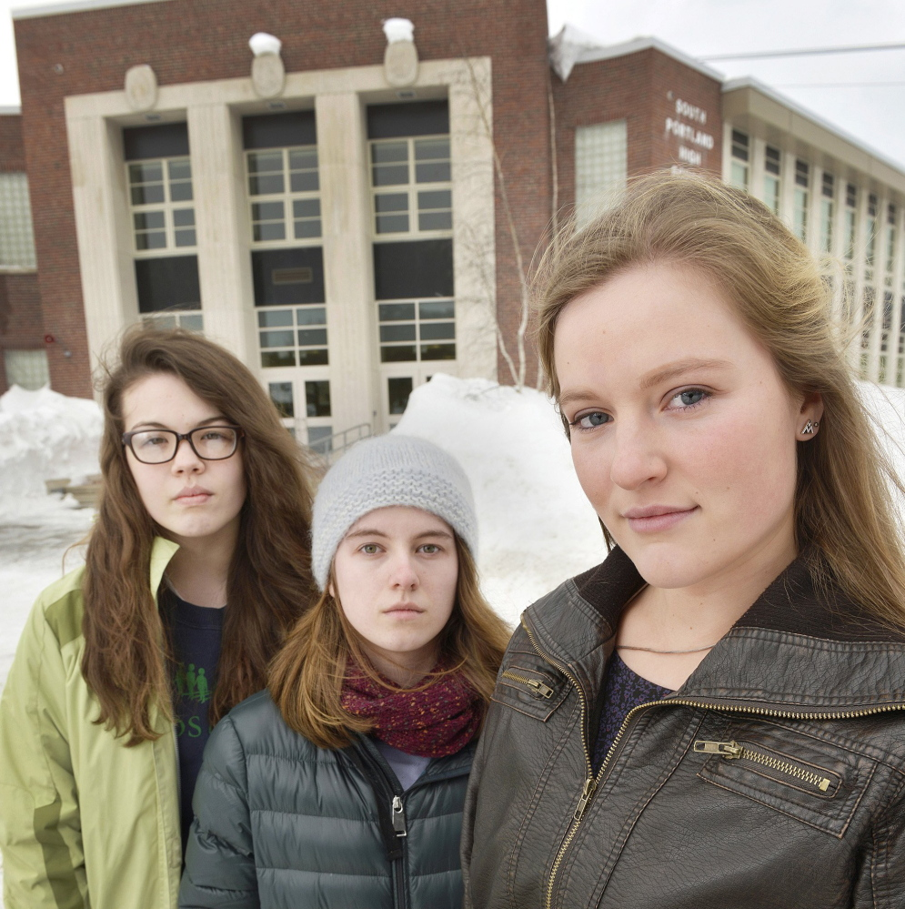 Lily SanGiovanni, right, is joined by Morrigan Turner, left, and Gaby Ferrell in front of South Portland High School, where they have let students and teachers know they don't have to say the Pledge of Allegiance.