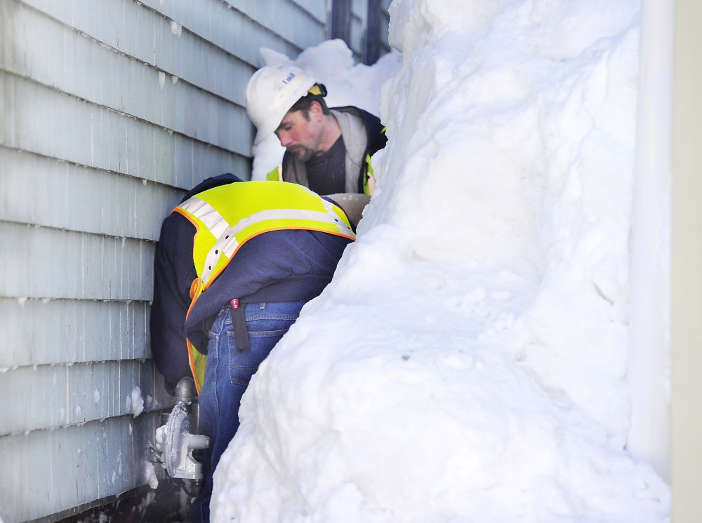 Workers from Unitil Corp. gas company repair the gas meter after clearing the snow from it at an apartment building on Congress Street on Portland's Munjoy Hill on Friday.