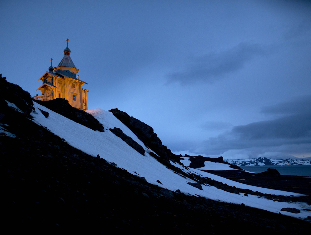 The Holy Trinity Church, perched on a rocky hill, is illuminated on King George Island, Antarctica. The Associated Press