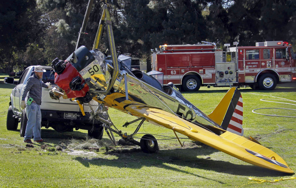 Associated Press The World War II-era trainer airplane that actor Harrison Ford crash-landed Thursday is removed from Penmar Golf Course in the Venice area of Los Angeles on Friday. Ford, 72, is hospitalized with undisclosed injuries that his publicist says are not life-threatening. The actor was flying the plane when it lost engine power shortly after takeoff from nearby Santa Monica, Calif., Municipal Airport.