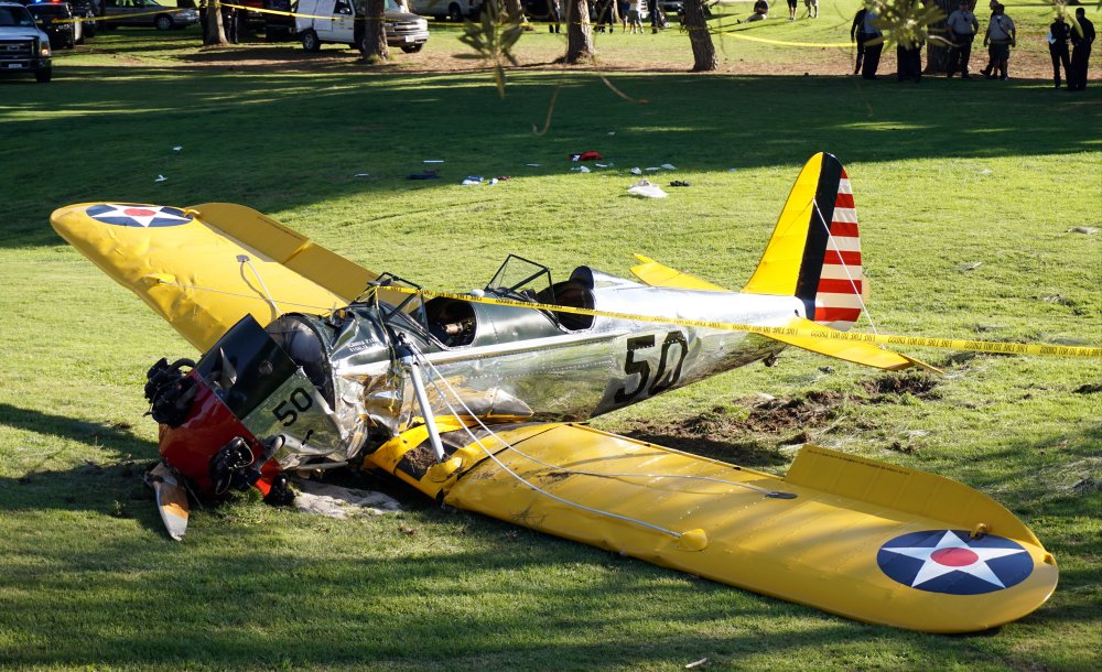 A small vintage airplane rests on the ground after actor Harrison Ford, below right, crash-landed on the Penmar Golf Course in the Venice area of Los Angeles on Thursday. The Associated Press