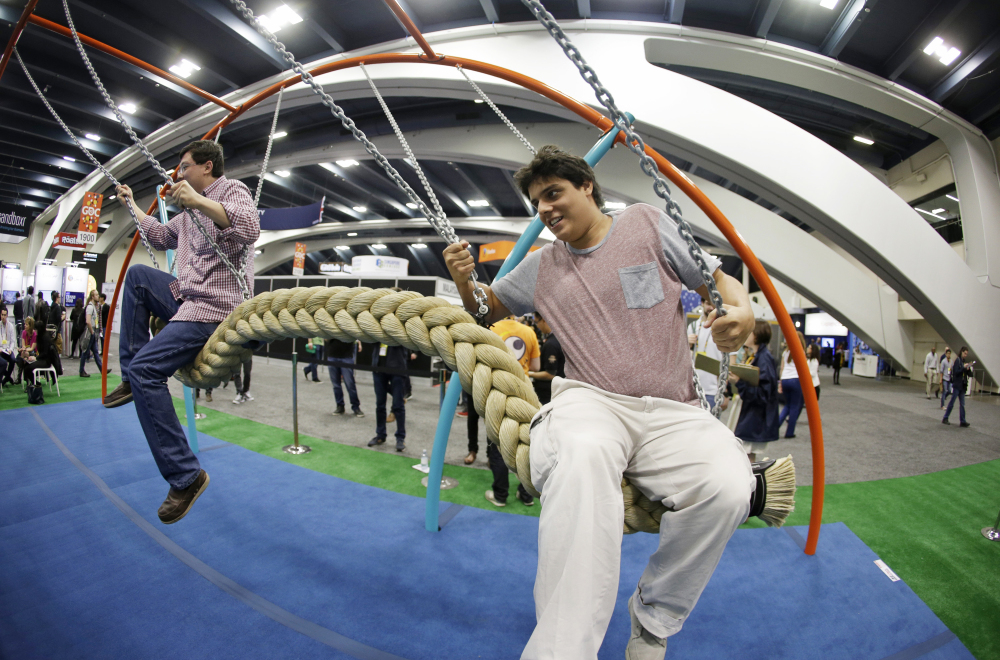 Phillip Chu Joy, left, and Juan Pablo Cabrejos Meza, right, ride a swing in the Biba smart playground at the Game Developers Conference, Wednesday, in San Francisco. The Associated Press