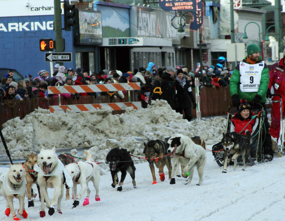 Musher Kelly Maixner, of Big Lake, Alaska, with a rider in his sled, participates in the ceremonial start of the Iditarod Trail Sled Dog Race in Anchorage, Alaska, on Saturday.