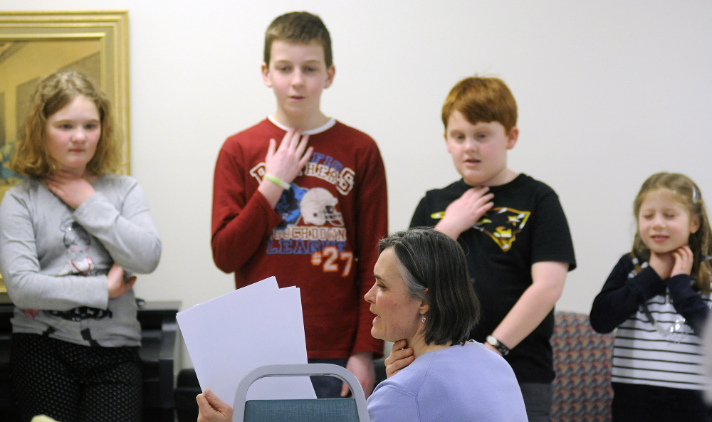 Karen Foust, the teacher for the Maine French Language Heritage Program, leads Augusta elementary school students enrolled in the program in a song Tuesday at the Chateau Cushnoc in Augusta.