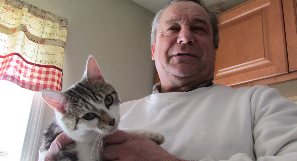 William Rattenni holds his cat Floki, who kept a nearby woman trapped in her house for two hours Thursday.