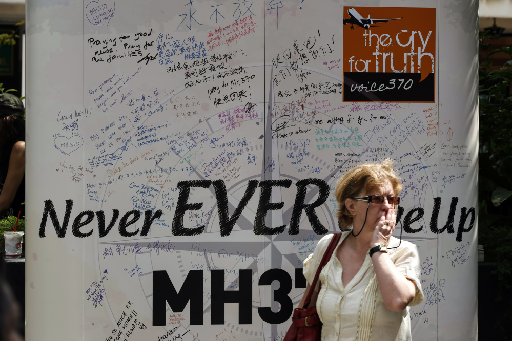 A visitor walks past a board with well-wishing messages during a remembrance event in a mall outside Kuala Lumpur, Malaysia, on Sunday. Families of the 239 people on board Malaysia Airlines Flight 370 on Sunday marked the anniversary of the plane's disappearance, vowing to never give up on the desperate search for wreckage and answers to the world's biggest aviation mystery.