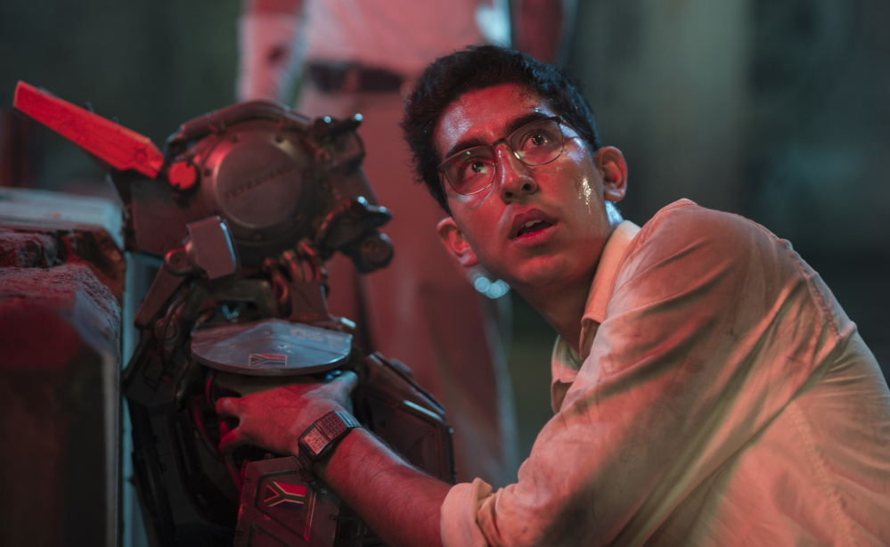 "Dev Patel appears worried in a scene from ""Chappie,"" a film about a police robot that learns how to think and feel."