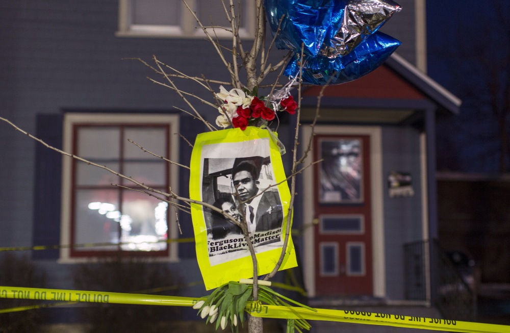 A makeshift memorial in front of a home cordoned off with barricade tape in Madison, Wis., pays tribute to a 19-year-old black man killed by police. Demonstrators marched Saturday to protest the killing.