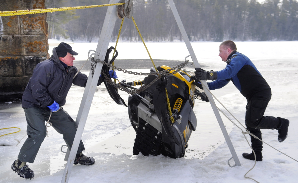 Matt Sinclair, right, and his father, David, secure a snowmobile they hoisted from under the ice on Maranacook Lake in Winthrop on Sunday.