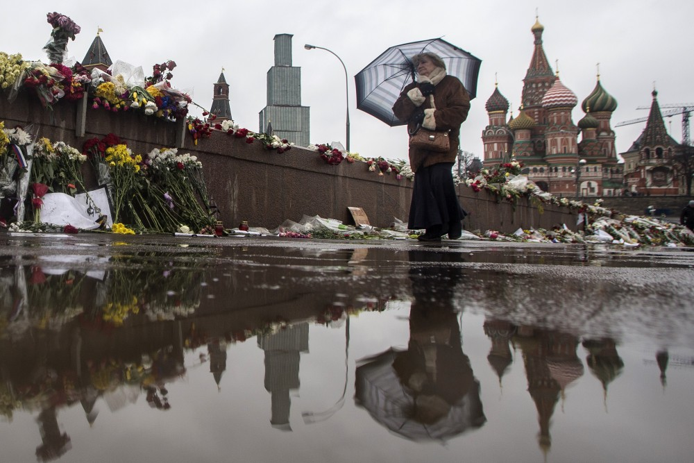An elderly woman passes the place where Boris Nemtsov, a charismatic Russian opposition leader and sharp critic of President Vladimir Putin, was gunned down on Feb. 27 near the Kremlin in Moscow.