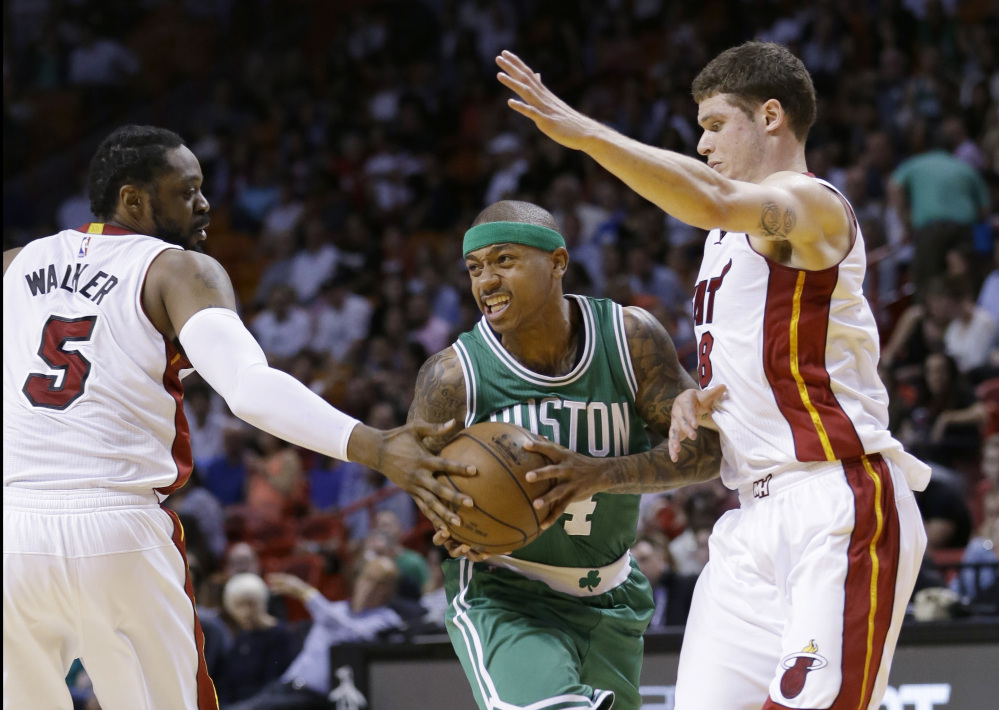Celtics guard Isaiah Thomas drives past Miami Heat guard Henry Walker (5) and guard Tyler Johnson, right, during the first half of Monday night's game in Miami. Thomas scored 25 points in the Celtics' 100-90 win.