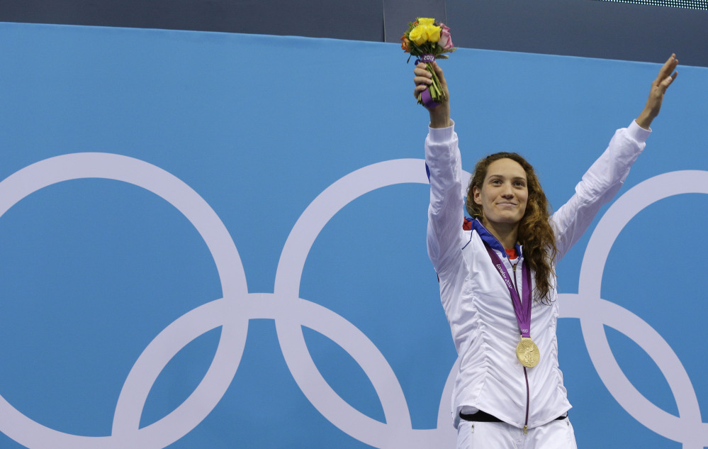 In this Sunday, July 29, 2012 file photo France's Camille Muffat celebrates with her gold medal for the women's 400-meter freestyle swimming final at the Aquatics Centre in the Olympic Park during the 2012 Summer Olympics in London.