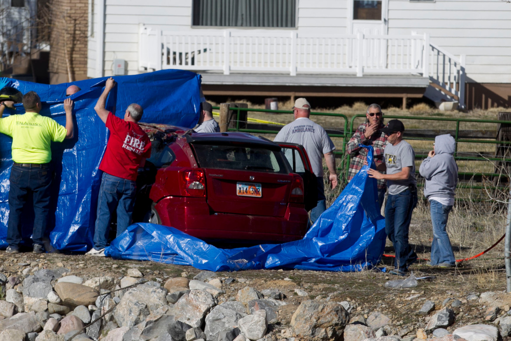 In this March 7, 2015 photo, officials respond to a report of car in the Spanish Fork River near the Main Street and the Arrowhead Trail Road junction in Spanish Fork, Utah.