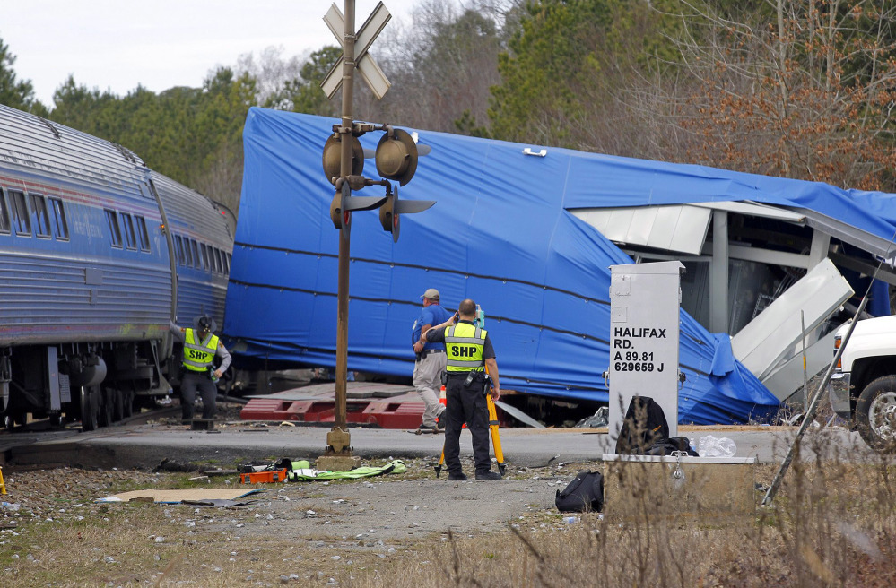 Police and others work the scene of a truck-train collision Monday in Halifax, N.C. The 16-foot-square electrical building that the truck was hauling was wrapped in blue plastic.