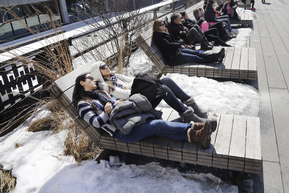 Visitors to the High Line elevated park in New York City rest on benches between piles of snow Monday, when the temperature reached 52 degrees in Manhattan, according to the National Weather Service. Cold weather is about to make a return.