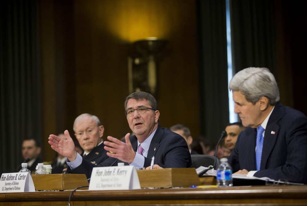 Defense Secretary Ash Carter, center, flanked by Secretary of State John Kerry, right, and Joint Chief Chairman General Martin Dempsey, testifies on Capitol Hill in Washington, Wednesday, March 11, 2015, before the Senate Foreign Relation Committee. Three of America's top national security officials face questions on Capitol Hill about new war powers being drafted to fight Islamic State militants, Iran's sphere of influence and hotspots across the Mideast. (AP Photo/Pablo Martinez Monsivais)