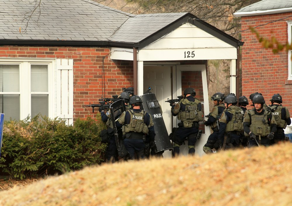 A police tactical team prepares to enter a home in the 100 block of Dade Avenue in Ferguson, Missouri, on as they search for a gunman who shot two police officers during a protest Thursday.