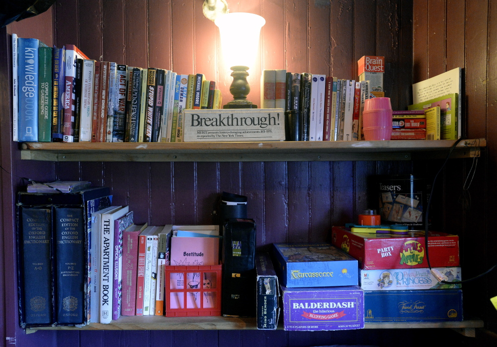 Books and games sit on the shelf at Mama's CrowBar on Munjoy Hill. The CrowBar has an eclectic decor and an unusual mix of entertainment, much of it customer-generated.