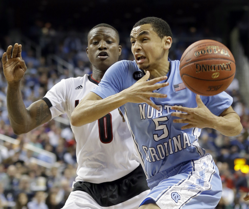 North Carolina's Marcus Paige loses the ball as Louisville's Terry Rozier defends during an Atlantic Coast Conference tournament quarterfinal in Greensboro, N.C. on Thursday night. Paige scored 13 points for the Tar Heels, who recovered from early missteps for a 70-60 win.