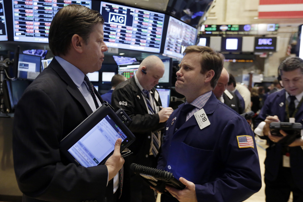 Traders Edward Schreier and John Elliott work on the floor of the New York Stock Exchange on Friday, when the Dow Jones industrial average fell 145.91 points.