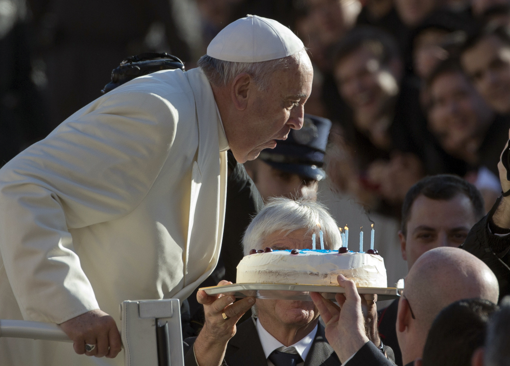Pope Francis blows out candles on a birthday cake on the occasion of his 78th birthday as he arrives for his weekly general audience in St. Peter's Square at the Vatican. The Pontiff marks his second anniversary riding a wave of popularity that has reinvigorated the Catholic Church in ways not seen since the days of St. John Paul II.  The Associated Press