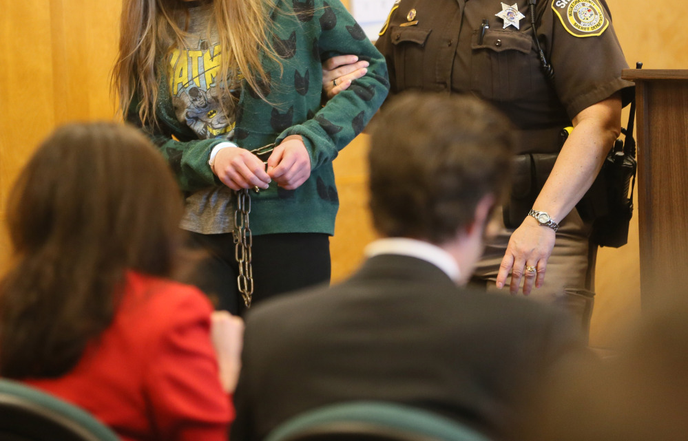 One of two girls, suspects in the Slender Man stabbing case, is escorted into court in Milwaukee on Friday. Her face is not shown because of her age.