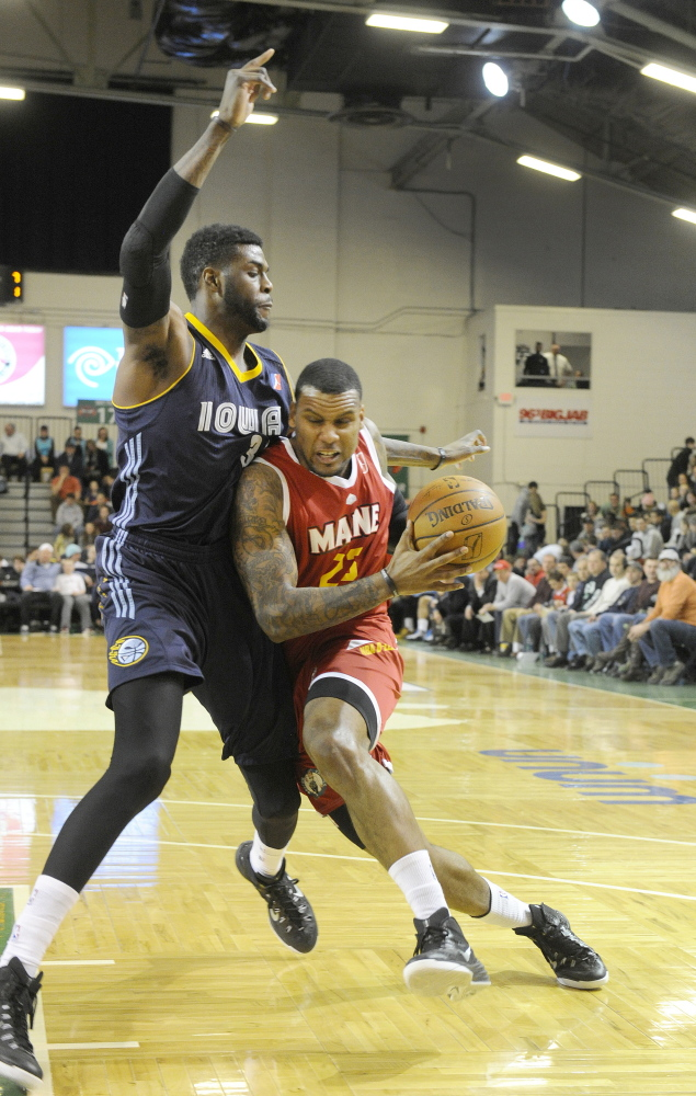 Romero Osby forces his way by Iowa's Willie Reed for a layup during Friday night's game at the Expo, won by the Red Claws in convincing fashion.