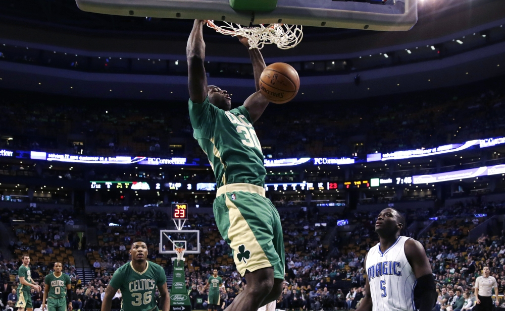 Celtics forward Brandon Bass slams a dunk as Orlando Magic guard Victor Oladipo looks on during the first quarter of Friday night's win by the Celtics in Boston.