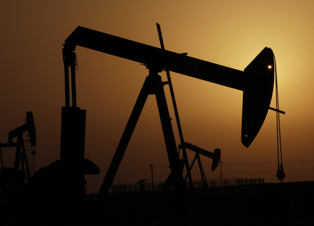 Pumps work in the desert oil fields of Sakhir, Bahrain, last year. Oil prices are likely to drop with no signs of slowing production in the U.S., according to a watchdog group.