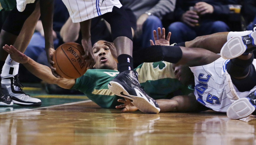 Celtics guard Avery Bradley reaches for the ball as he tangles with Orlando's Victor Oladipo. Boston rallied from an 11-point deficit to beat the Magic, 95-88.