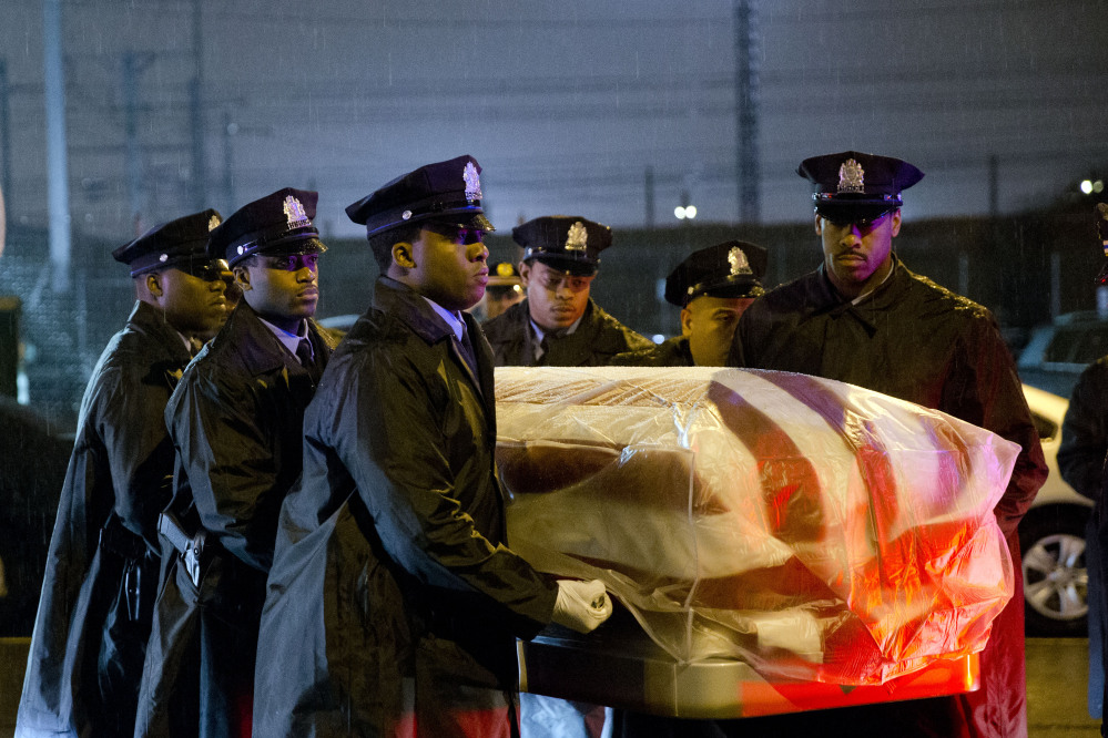 The remains of Philadelphia Police Officer Robert Wilson III are transferred to a horse-drawn hearse during a winter rainstorm on Saturday in Philadelphia. Wilson was shot and killed March 5 after he and his partner exchanged gunfire with two suspects trying to rob a video game store.