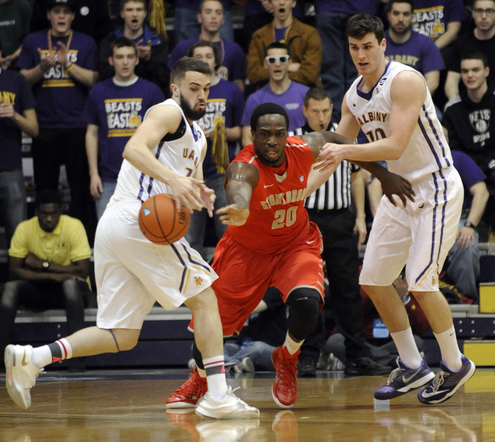 Albany's Peter Hooley, left, deflects the ball away from Stony Brook's Jameel Warney Jr. in the first half of Saturday's America East title game. Albany won on Hooley's 3-pointer in the final seconds.