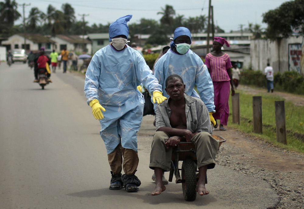 In this file photo taken on Sunday Sept. 28, 2014, residents of the St. Paul Bridge neighborhood wearing personal protective equipment take a man suspected of carrying the Ebola virus to the Island Clinic in Monrovia, Liberia.