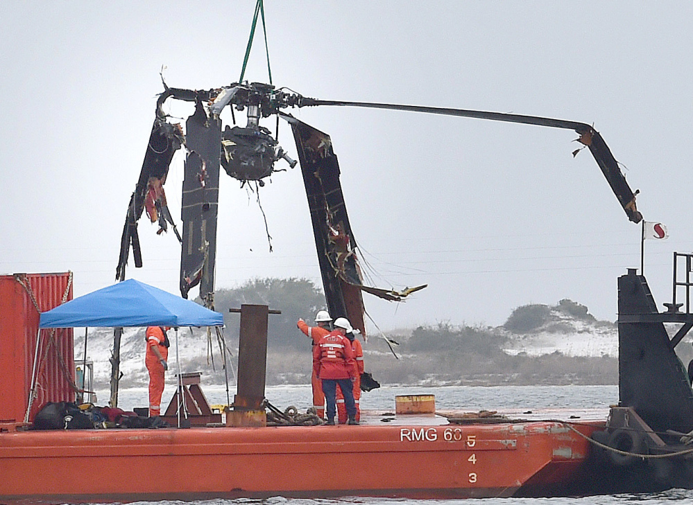 Crews lower a piece of a Black Hawk helicopter onto a barge Friday in Navarre, Fla. The helicopter carrying 11 servicemen crashed in dense fog during a training mission Tuesday.