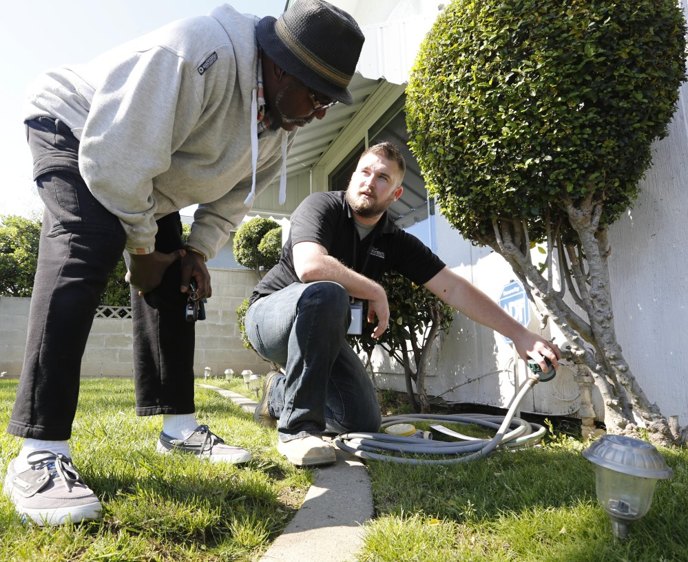 Steve Upton, an inspector for the water conservation unit of the Sacramento Utilities Department, right, shows Larry Barber how to use the water timer he installed on a spigot.