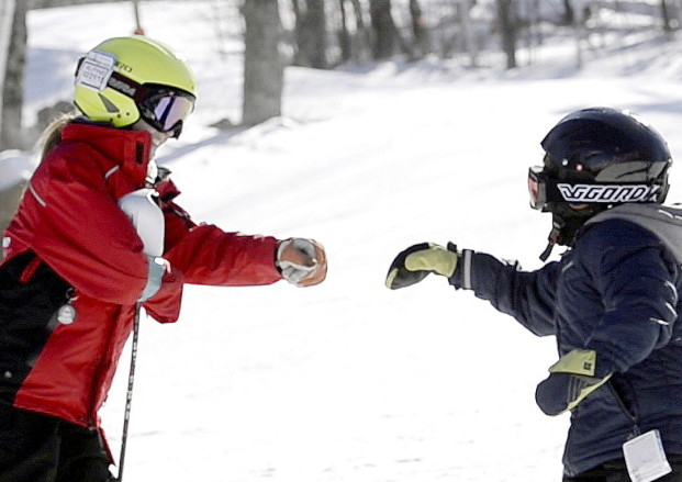 Keegan Moreau, 16, left, fist-bumps David Botana, 12, after a run down the mountain at Sunday River in Newry.