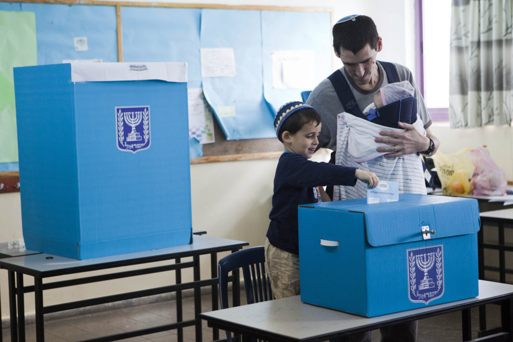 An Israeli settler votes, with the help of a child, in the settlement of Efrat, West Bank, Tuesday.